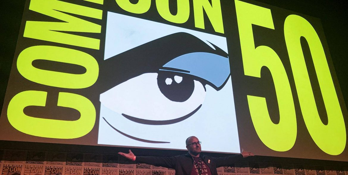 Fictitious host Adron Buske in front of the San Diego Comic-Con 50th anniversary logo on a huge screen at the Horton Grand Theatre